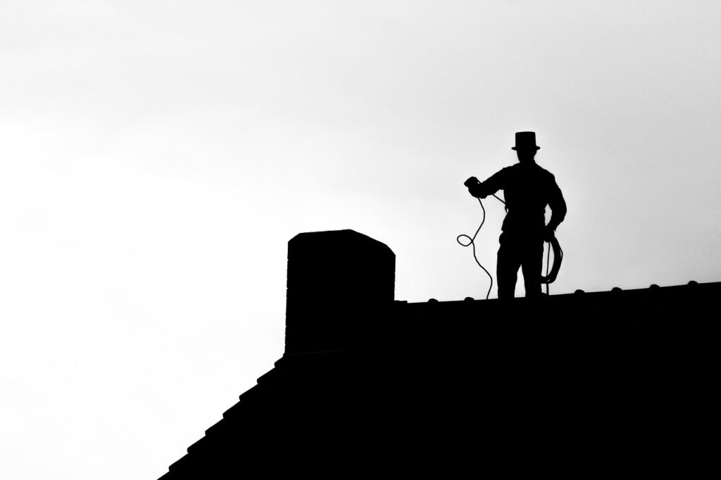 man on a roof inspecting the chimney